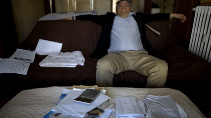 Man lying on couch after checking accounts, family budget, shocked by debt