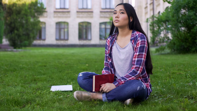 Thoughtful asian female student sitting on lawn alone and missing parents
