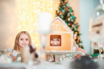 Two twin sisters at a table in the kitchen playing with a ginger house for the New Year. The kitchen in bright colors is decorated for Christmas