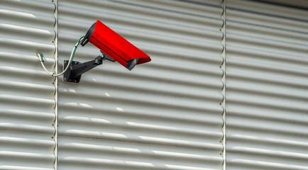 Überwachungskamera an einer Wellblechfassade