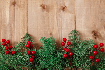 Christmas fir tree on wooden background. Red berries.