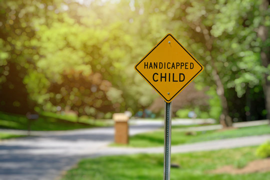 Yellow handicapped child street sign in a beautiful residential area.