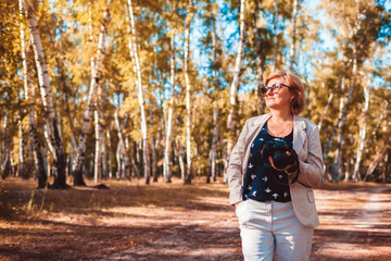 Middle-aged woman taking pictures using camera in autumn forest. Senior woman walking and enjoying hobby