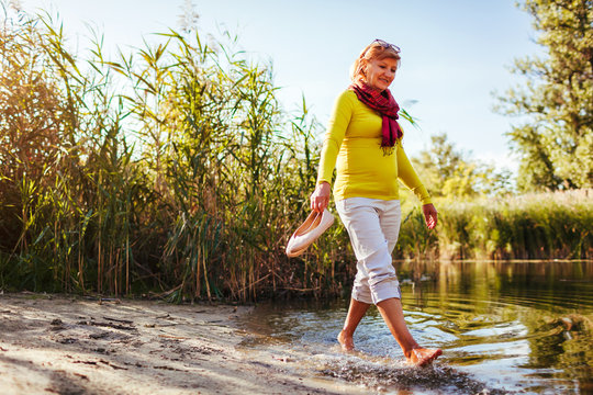 Middle-aged woman walking on river bank on autumn day. Senior lady having fun in the forest enjoying nature