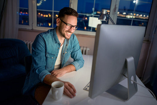 Man working on computer at home at night
