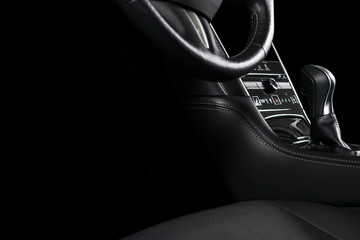 Modern Luxury car inside. Interior of prestige car. Comfortable leather seats. Black perforated leather cockpit with stitching. Steering wheel and dashboard. Automatic gear stick shift. Car detailing