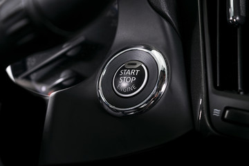 Car dashboard with focus on engine start stop button. Modern car interior details. Car detailing