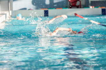 Group of children swimming crawl in pool, youth athletic school