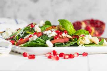 Salad. Spring vegetable salad. Fresh vegetable salad with grilled peach, pomegranate, spinach and fresh cheese