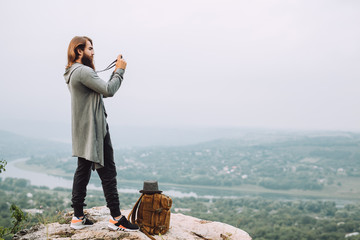 Bearded tourist makes a photo of a beautiful landscape.Near the guy is a stylish brown backpack and fashionable hat.Guy has long beautiful hair and well-groomed beard.