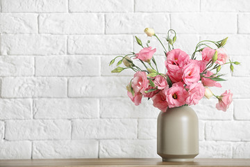 Vase with beautiful flowers on table against brick wall, space for text