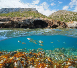 Spain Mediterranean coast a large cave on the sea shore with fish underwater, split view above and below water surface, Cova Tallada, Costa Blanca, Javea, Alicante, Valencia