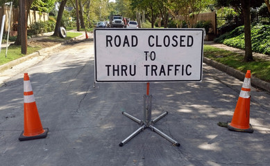 ROAD CLOSED TO THRU TRAFFIC sign in middle of neighborhood street.