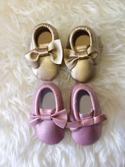 Little baby gold and rose shoe on white fluffy background