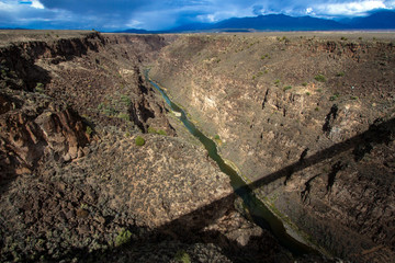 The bridge over the Rio Grande Gorge casts a long shadow across its 800' deep canyon, which lies on the Taos Plateau in New Mexico; looking north from US Hwy 64