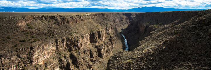 Panoramic view of the Rio Grande Gorge, looking south from the US Hwy 64 bridge over the 800' deep chasm, which lies on the Taos Plateau in New Mexico, paralling the Sangre de Cristo Mountains