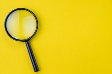 Black magnifying glass, magnifier on yellow background with copy space using as search, transparent, science discovery or SEO concept