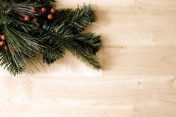 Faux fir tree branch and berries on wood background