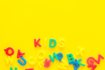 Early childhood development concept. Word kids written by plastic letters of toy alphabet on yellow background top view copy space