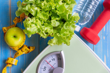 Diet and Healthy life Concept. Green apple and Weight scale measure tap with fresh vegetable, clean water and sport equipment for women diet slimming