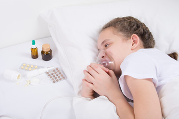 girl in bed, doing inhalation, putting on a mask in bed and looking at medication-tablets
