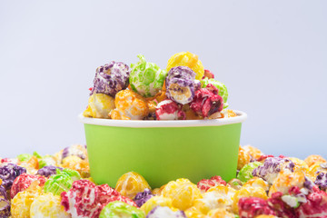 Foto op Aluminium Buffet, Bar a bucket of multi-colored popcorn stands in a pile of cereal, on a white background