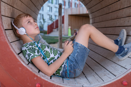 smiling boy with smartphone and headphones listening to music or playing game