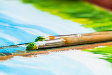 Paint brushes on the background of the paintings. Closeup, selective focus