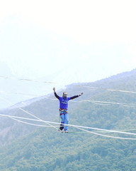 Highliner on a rope. Highline on a background of mountains. Extreme sport on the nature. Balancing on the sling. Equilibrium at altitude.