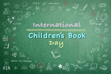 International Children's Book day greeting with doodle on grunge green chalkboard