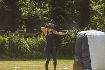 Woman practicing archery at boot camp