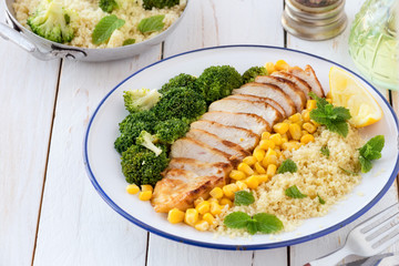 Deconstructed healthy chicken and couscous salad with broccoli florets and corn or Buddha bowl