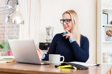 Portrait of smiling woman at her desk looking at laptop