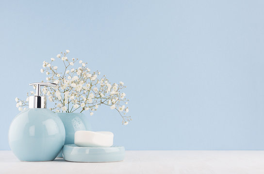 Fresh spring decor for bathroom with small white flowers, ceramic vase and soap pump bottle on white wood board.