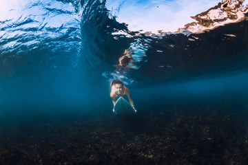 Underwater view of surfer girl with surfboard dive under barrel wave