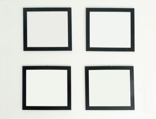 Four identical empty frames hang on white wall