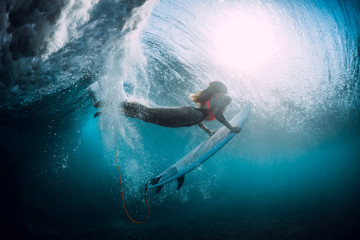 Surfer girl with surfboard dive underwater with under barrel ocean wave.