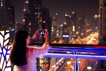 Girl taking a photo of Dubai cityscape