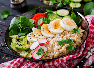 Healthy salad of fresh vegetables - tomatoes, avocado, cucumber, radish, egg, arugula and oatmeal on bowl. Diet food.