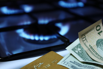money and bank cards on the background of the gas stove