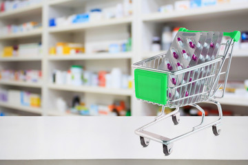 medicine pills capsule in shopping cart on pharmacy store counter with blur drugstore shelves defocused background