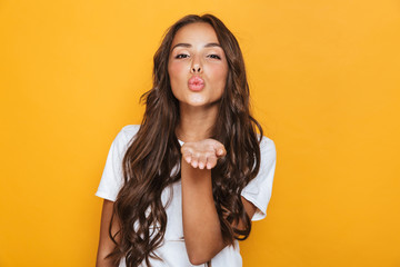 Happy young pretty woman posing isolated over yellow background blowing kisses.