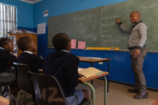 Male teacher teaching students in the class