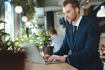 side view of focused businessman using laptop at table in cafe