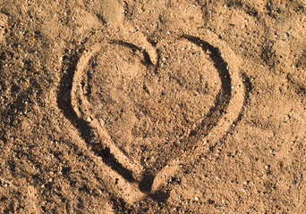Heart in the sand on the beach at summer sunset