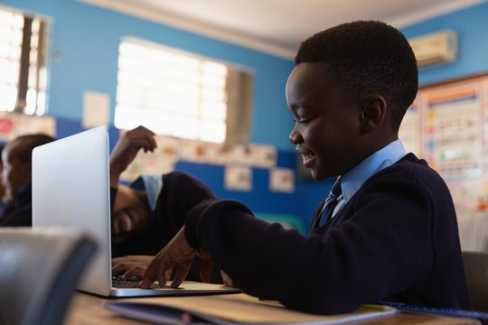 Smiling student using laptop in classroom