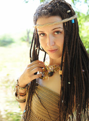 Beautiful sexy boho style woman with dreadlocks portrait, looking at camera, against sunny summer