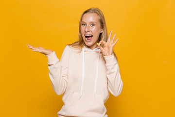 Photo of lovely girl 16-18 with dental braces holding copyspace at palm, isolated over yellow background
