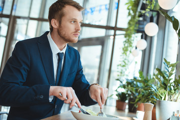 side view of pensive businessman in suit looking away while having lunch in cafe