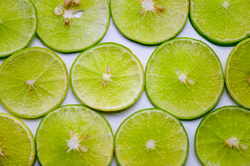 Lime fruit sliced and placed on white table.
